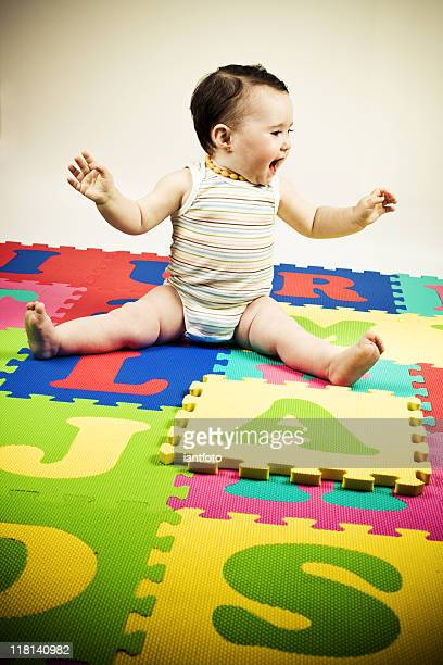 Baby playing on a colorful alphabet.