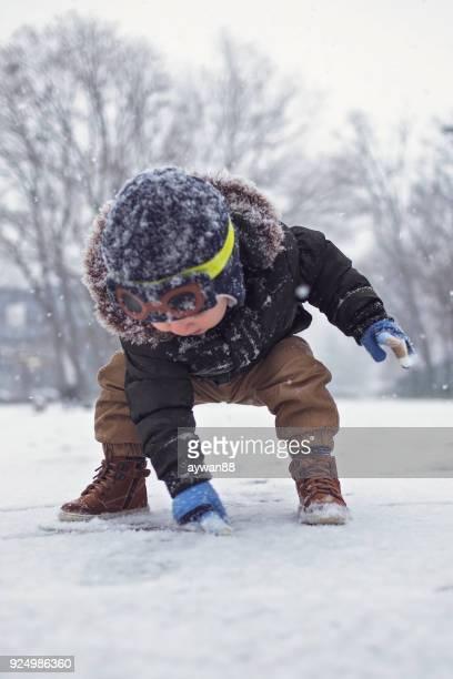 ベビー外遊び雪の中 - first occurrence ストックフォトと画像