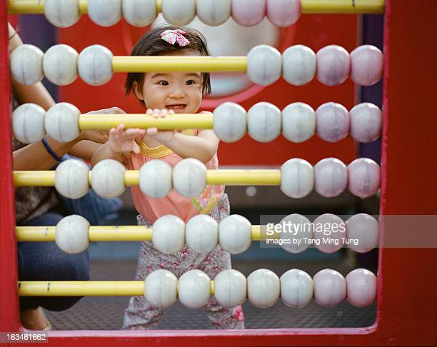 Baby playing with a giant abacus in the playground