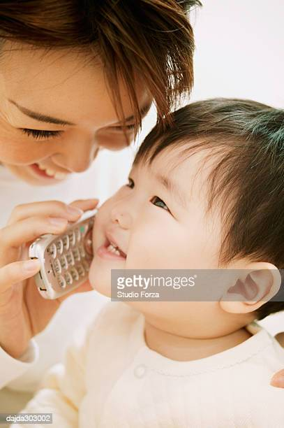 A Baby Playing with a mobile phone