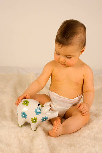 Baby playing with a piggybank.