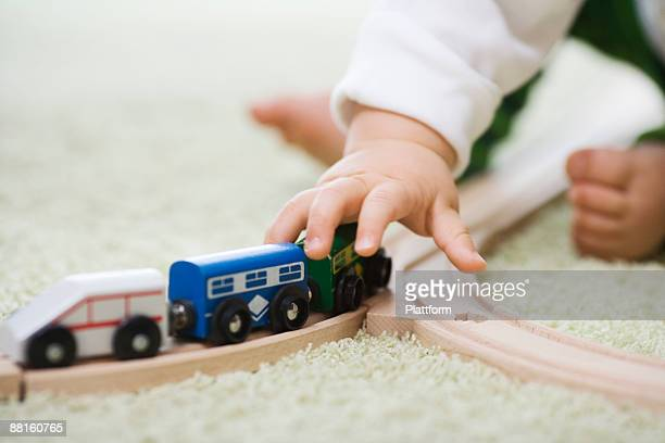A baby playing with a train.