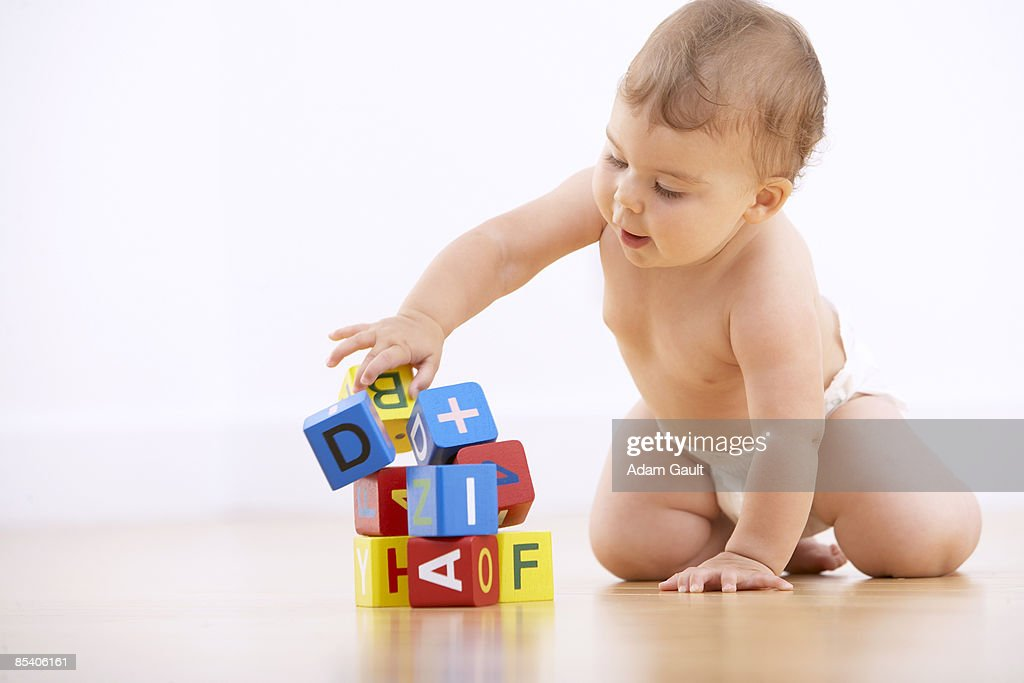 Baby playing with alphabet blocks : Stock Photo