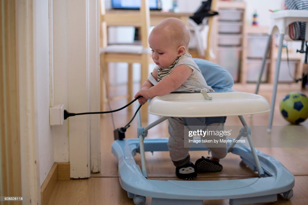 Baby playing with electricity cord at home : Stock Photo