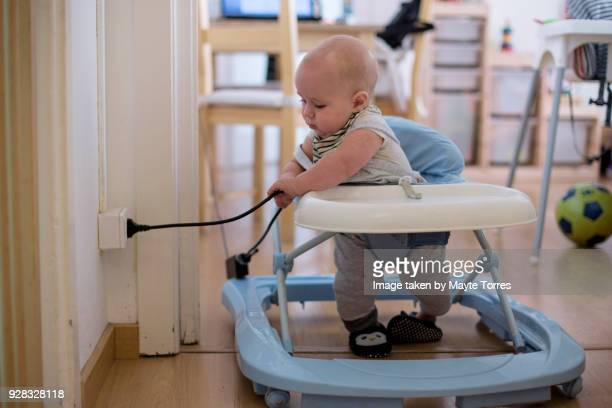 baby playing with electricity cord at home - danger stock photos and pictures