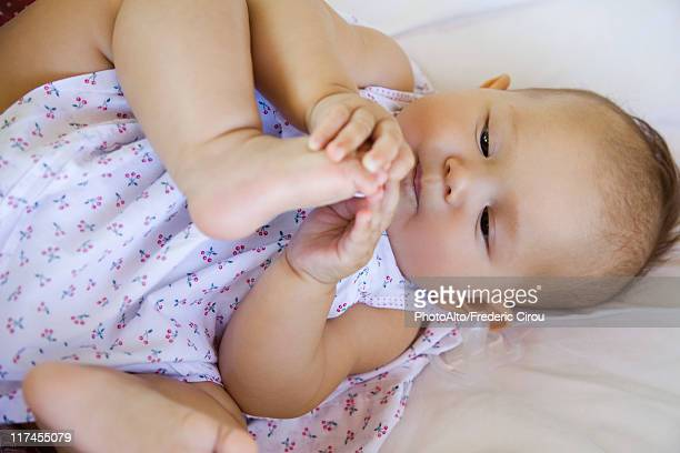 Baby playing with foot, portrait