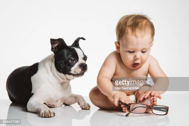 Baby playing with glasses sitting next to dog