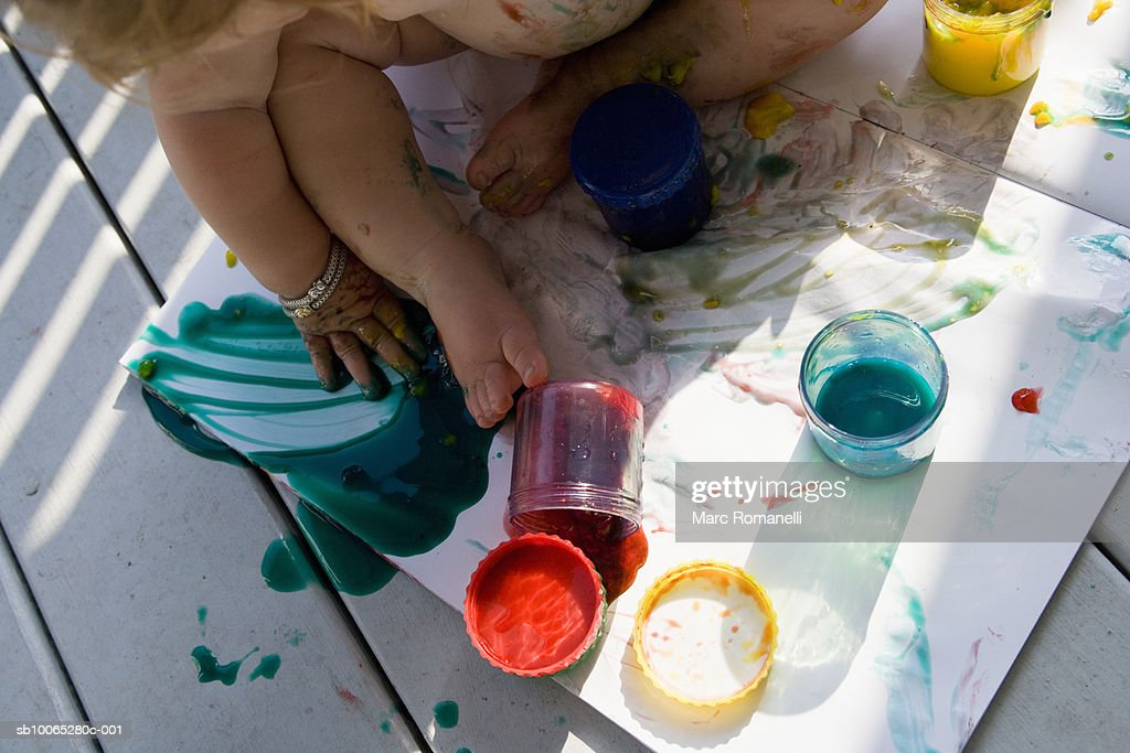 Baby (9-12 months) playing with paint, low section : Foto stock