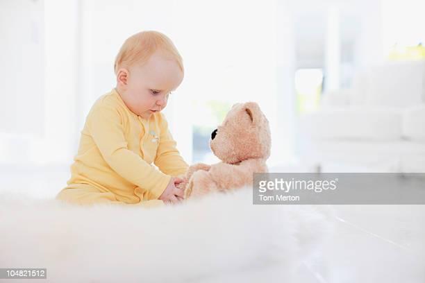 Bébé jouant avec ours en peluche sur tapis