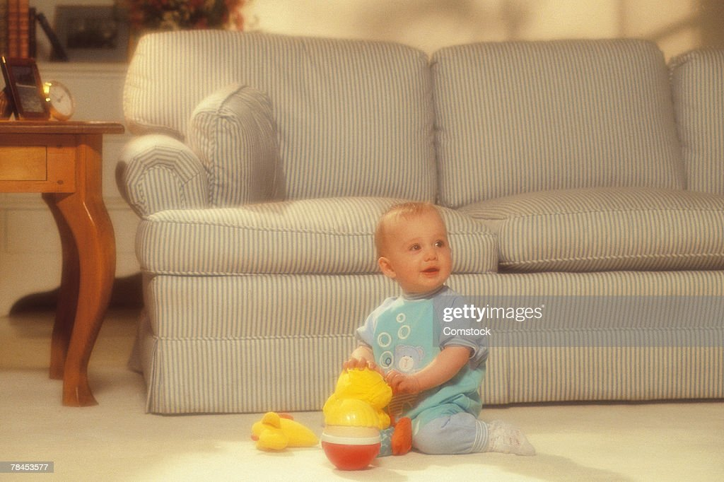 Baby playing with toys in living room : Stockfoto