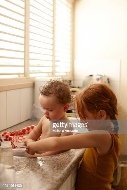 Baby playing with younger red headed sister in sink looking down at water
