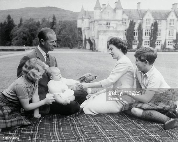 Baby Prince Andrew perches on Prince Philip's lap during a picnic on the grounds of Balmoral Castle Looking on are Queen Elizabeth Prince Charles and...