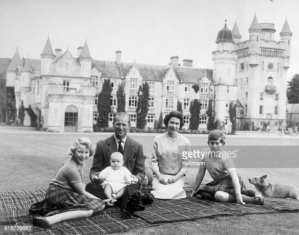 Baby Prince Andrew perches on Prince Philip's lap during a picnic on the grounds of Balmoral Castle. Also pictured are Queen Elizabeth, Prince...