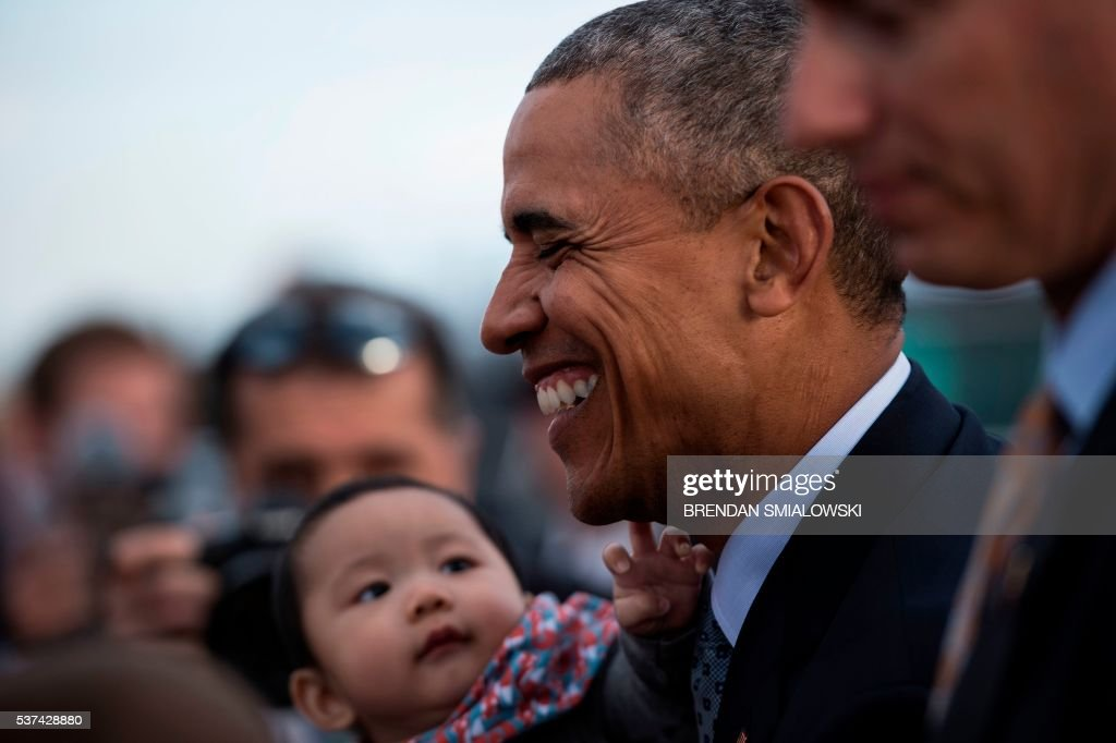 TOPSHOT - A baby reaches for US President Barack Obama while he greets people after arriving at Peterson Air Force Base June 1, 2016 in Colorado Springs, Colorado. / AFP / Brendan Smialowski