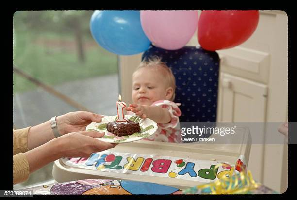 Baby Reaching for Cake and Birthday Candle
