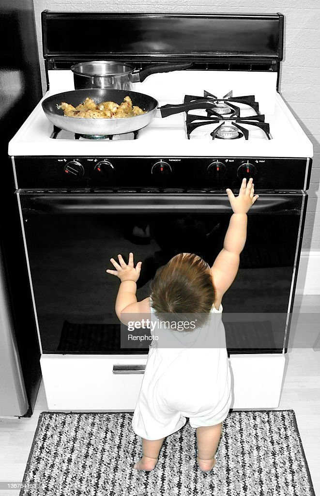 Baby Reaching for Stove : Bildbanksbilder