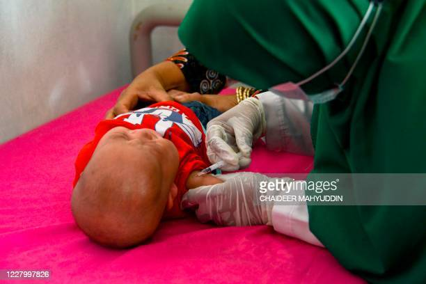 Baby receives the Bacillus CalmetteGuerin vaccine for tuberculosis at an integrated services post in Banda Aceh on August 11, 2020.