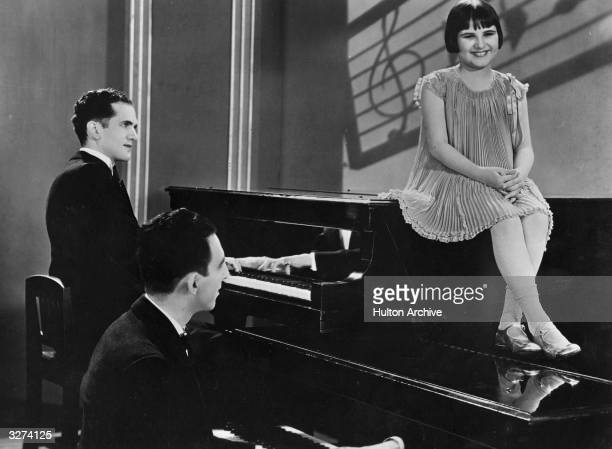 Baby Rose Marie the child actress sits on one piano resting her feet on another while two gentlemen play in a scene from the film 'International...