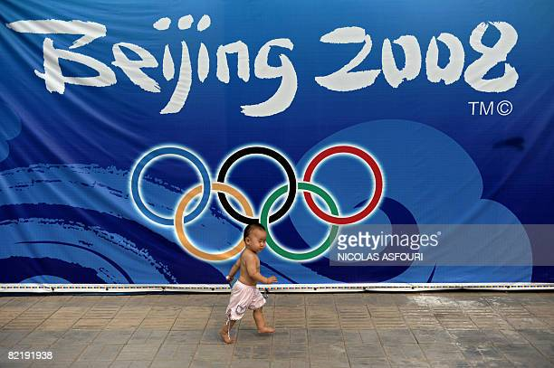 A baby runs ahead of his mother past the 2008 Beijing olympic games' logo in a street of Beijing on August 6 2008 The 2008 Beijing Olympic games will...