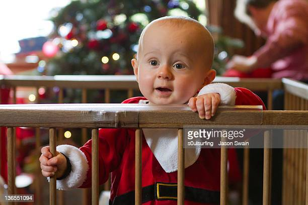 baby santa in playpen - s0ulsurfing stock pictures, royalty-free photos & images