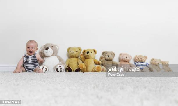 baby sat with line of teddy bears - one baby boy only stock pictures, royalty-free photos & images