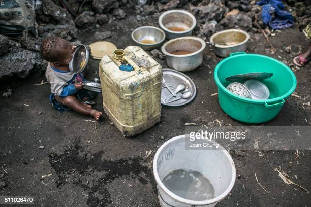 A baby scrapes what is left in a bowl after the mother was unable to wash dishes for a long time due to lack of water in Mugunga I IDP camp on June...
