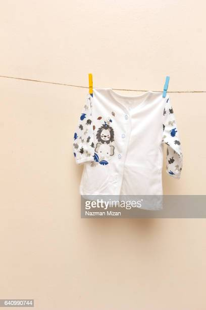 Baby shirt with animal patterns on clotheslines.
