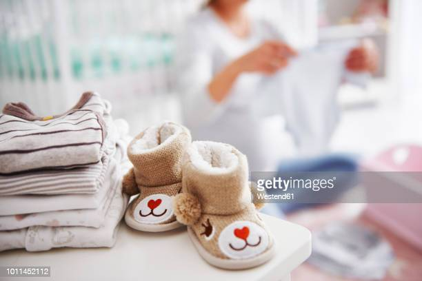 baby shoes and pregnant woman with baby clothes in baby room - baby booties stock photos and pictures