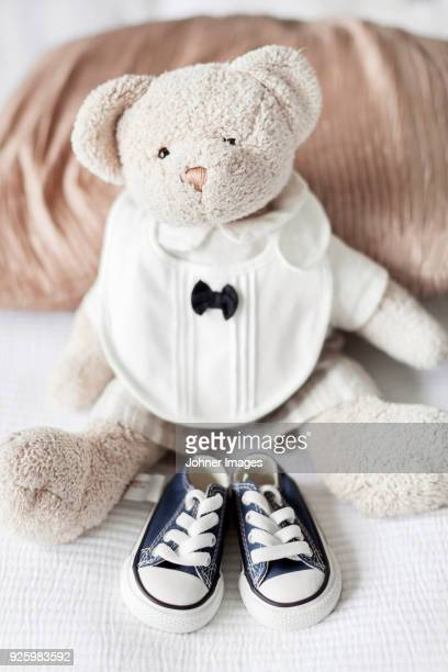 Baby shoes lying beside teddy bear