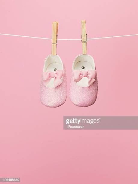 baby shoes on clothes line - hanging stock pictures, royalty-free photos & images