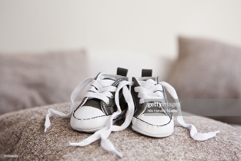 Baby shoes on pillow : Stock Photo