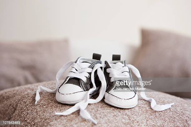 baby shoes on pillow - baby booties stock photos and pictures