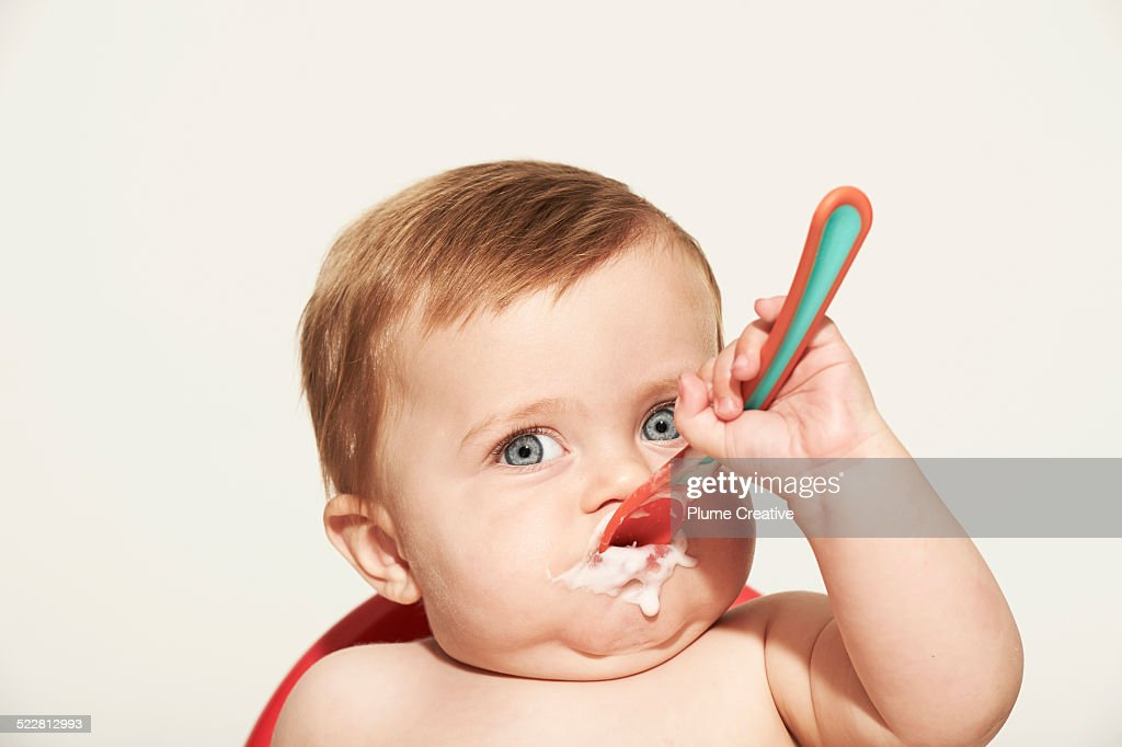 Baby shoving food in his face : Stock Photo