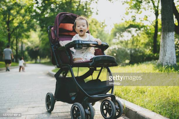 baby sit down in baby carriage - pushchair stock pictures, royalty-free photos & images