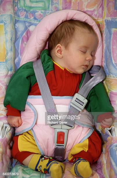A baby sits in a car child seat with a safety harness