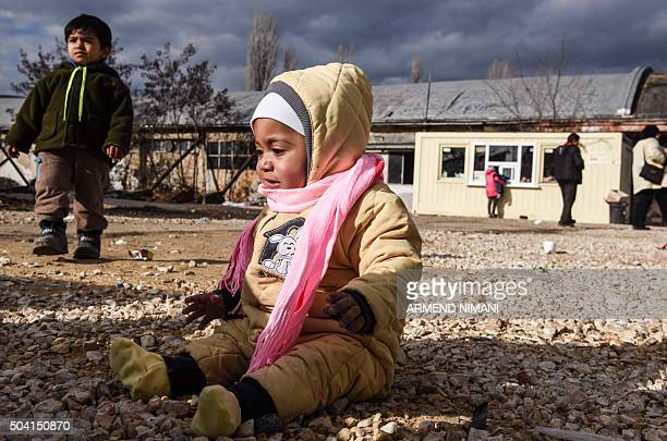 Baby sits on the ground as migrants and refugees wait for a bus at a transit camp in the southern Serbian town of Presevo on January 9, 2016. More...
