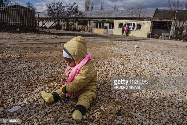 A baby sits on the ground as migrants and refugees wait for a bus at a transit camp in the southern Serbian town of Presevo on January 9 2016 More...
