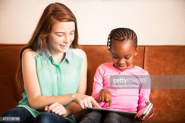Baby sitter playing with preschooler using tablet mobile phone