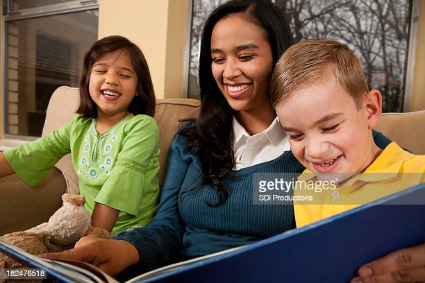 Baby Sitter Reading to Two Children Laughing