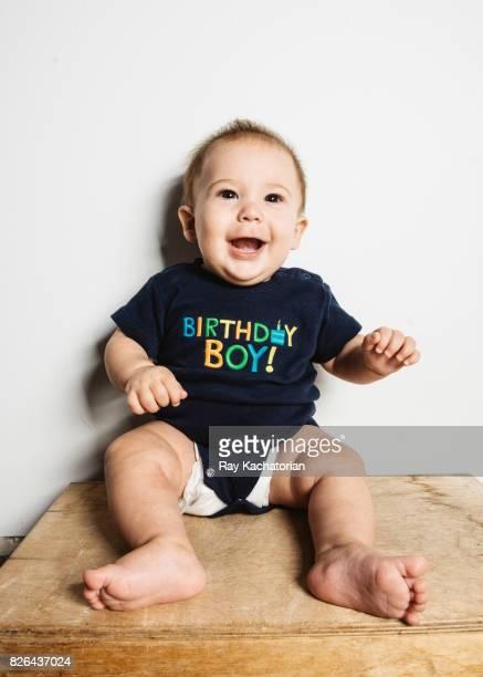 Baby sitting against wall wearing Happy Birthday