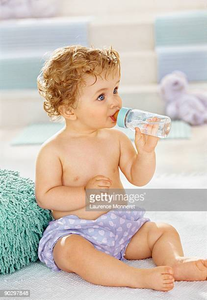 Baby sitting and drinking water in a baby bottle