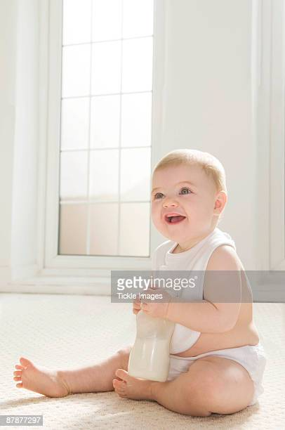 A baby sitting holding a milk bottle.