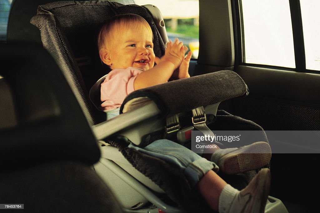 Baby sitting in a car seat and clapping hands : Stockfoto