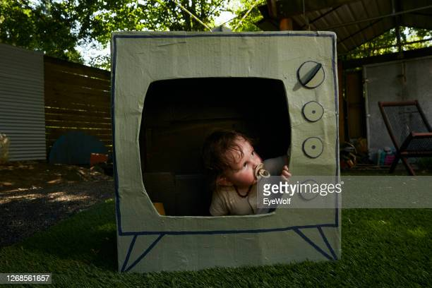 a baby sitting in a cardboard tv looking out. - insight tv ストックフォトと画像