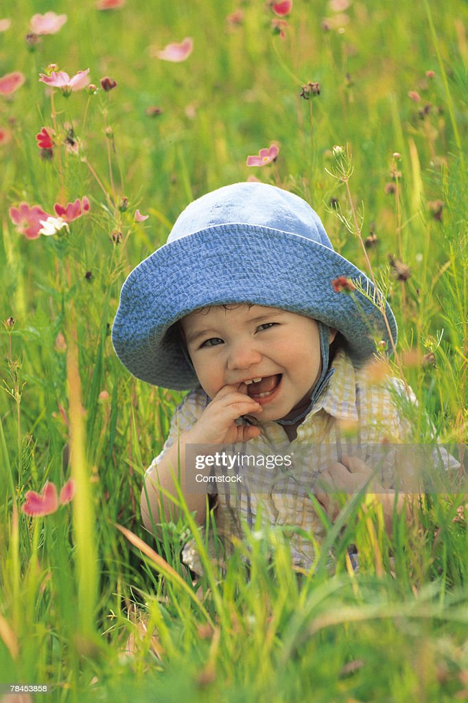 Baby sitting in a meadow : Stockfoto