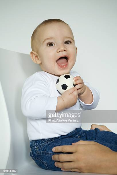 Baby sitting in chair holding ball, mother's hands holding baby's legs