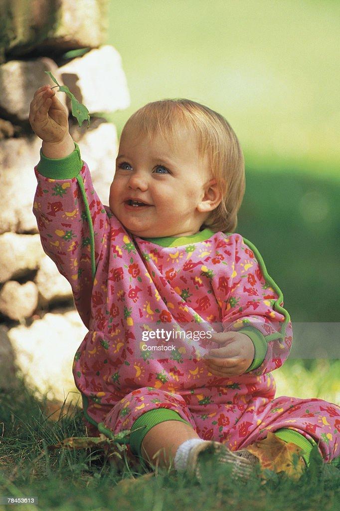 Baby sitting in grass : Stockfoto