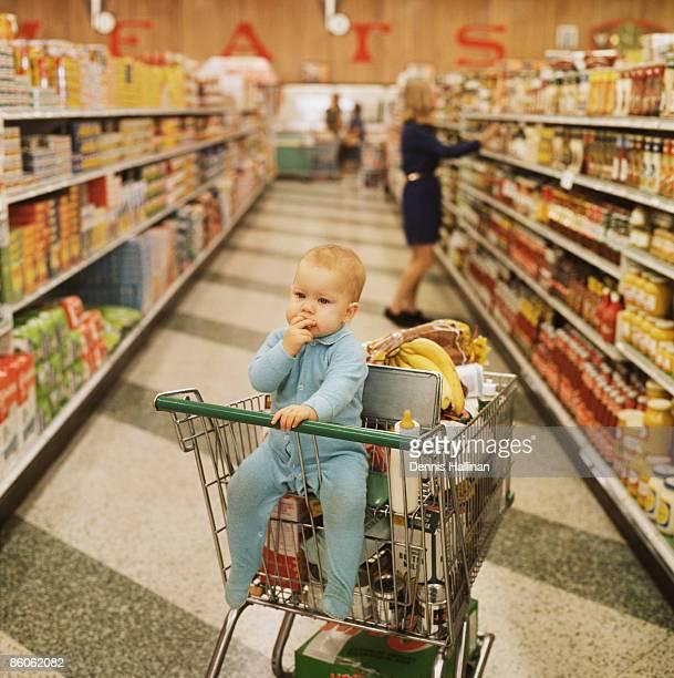 Baby sitting in supermarket shopping cart