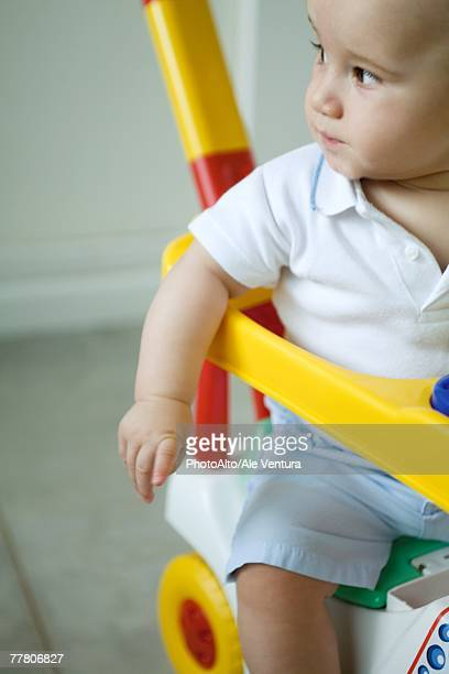 Baby sitting in toy stroller, looking away