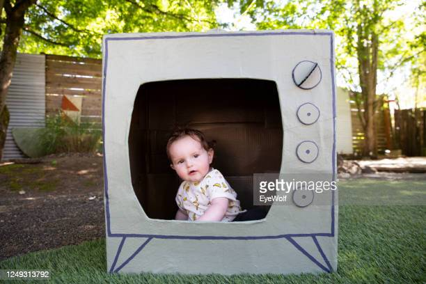 a baby sitting in tv made from a cardboard box, looking off camera playfully. - insight tv stock-fotos und bilder